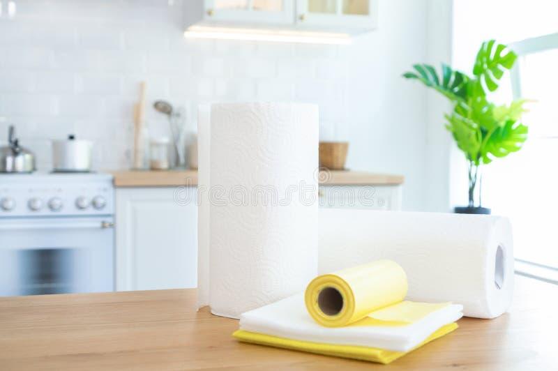Rolls von Papierhandtüchern, von Reinigungstüchern und von Abfalltaschen auf dem Tisch in der Küche mit Sonnenlicht lizenzfreie stockbilder