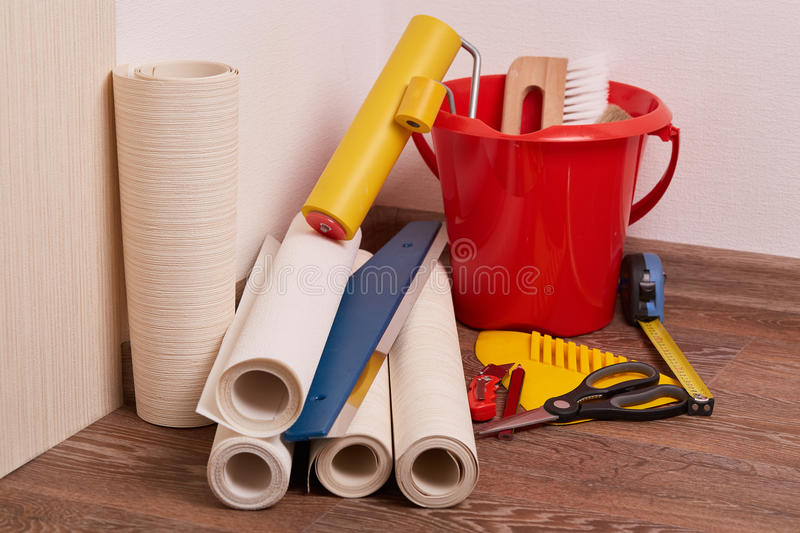 Rolls of wallpapers and various tools for wallpapering. Still life from rolls of wall-paper and various tools for wallpapering. Repair. Home renovation stock images