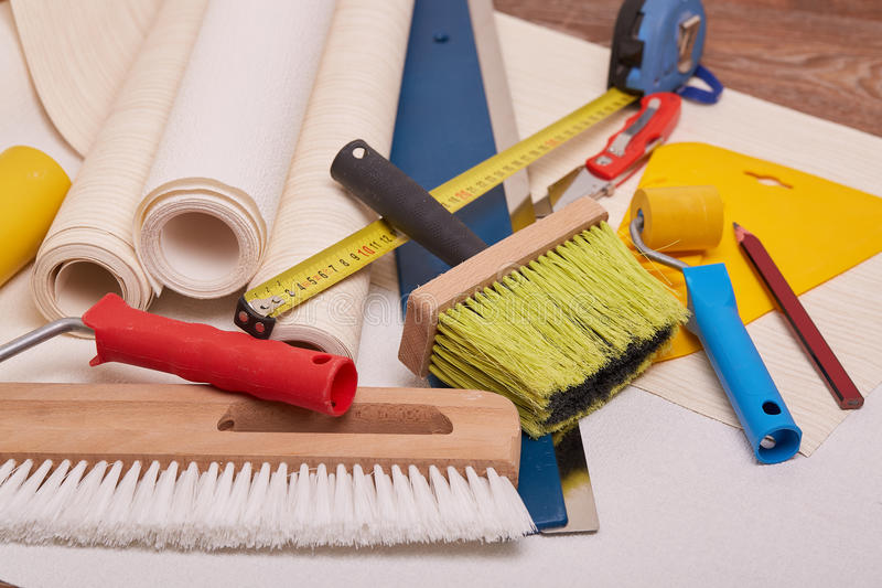 Rolls of wallpapers and various tools for wallpapering. Still life from rolls of wall-paper and various tools for wallpapering. Repair. Home renovation stock image
