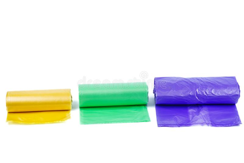 Rolls of yellow, green and purple plastic garbage bags stock photos