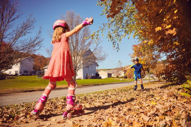 Rollschuhlaufen des kleinen Mädchens zu ihrem männlichen Freund stockbild