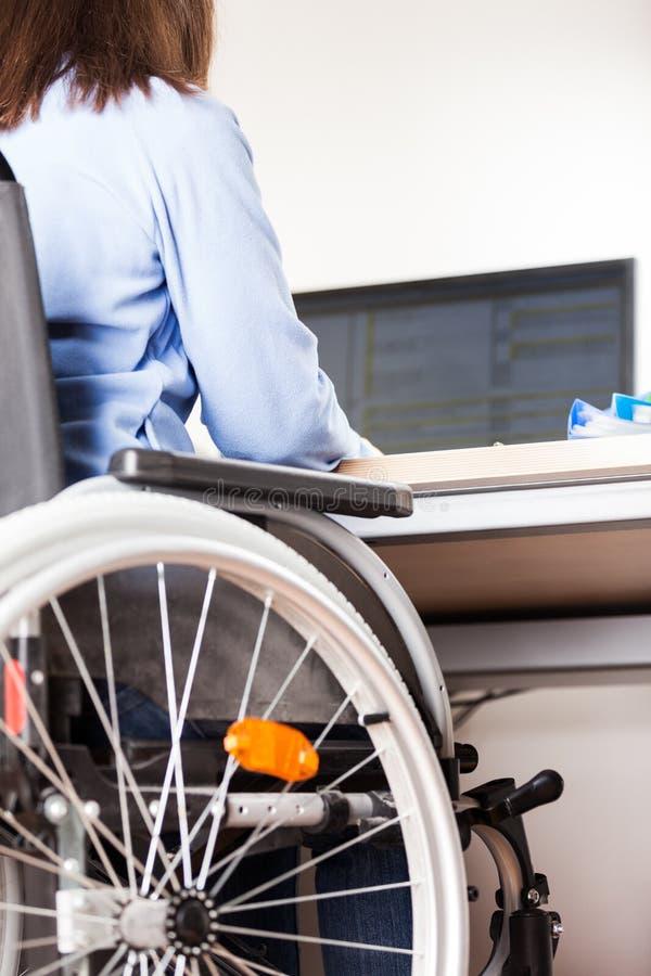 Rollstuhlarbeitsschreibtischcomputer der ungültigen oder behinderten Frau sitzender lizenzfreie stockbilder