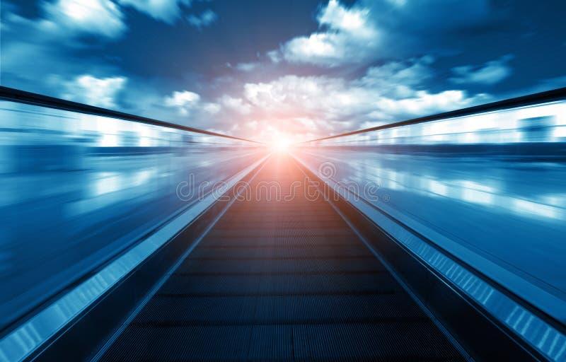 Rolltreppe, die zu die entfernte Leuchte führt stockbild