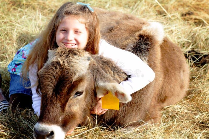 Rolnej dziewczyny i zwierzęcia domowego uśmiechnięta łydka fotografia stock