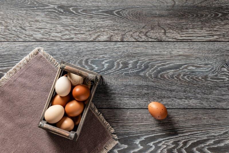 Rolni świezi organicznie wielcy brązu i białych jajka w jajecznej drewnianej skrzynce na nieociosanym ciemnym dębowego drewna tła zdjęcia stock