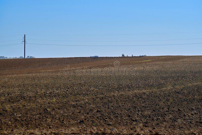 Rolnictwa pole z niebieskim niebem i liniami energetycznymi Wiejska natura w rolnej ziemi Słoma na łące zdjęcia stock