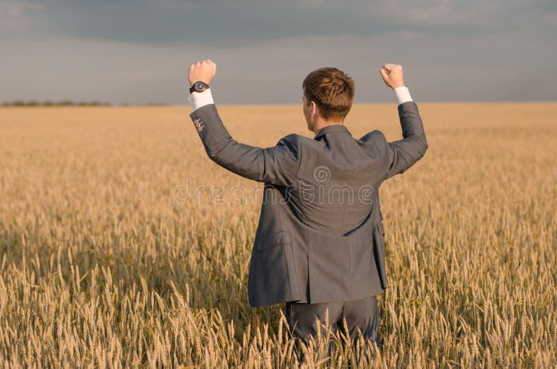Rolnictwo, szczęśliwy rolnik gestykuluje w pszenicznym polu przygotowywającym żniwo, z rękami up i kciukiem zdjęcia stock