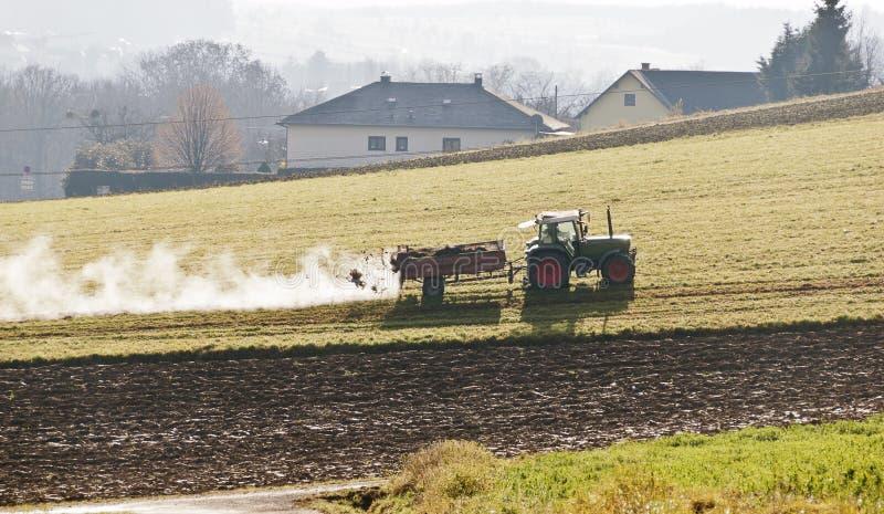 rolnik nawozi łąkę z łajnem fotografia stock