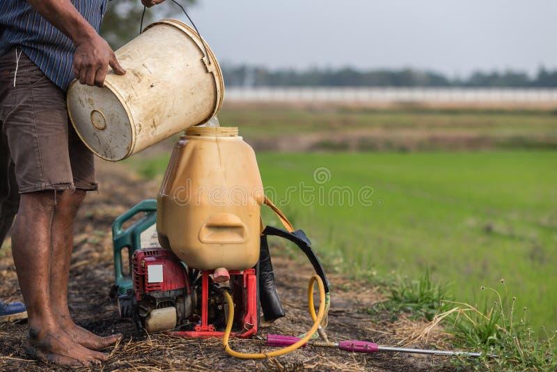 Rolnik przygotowywa substancję chemiczną natryskowy zbiornik przed kiścią zielenieć yo obraz stock