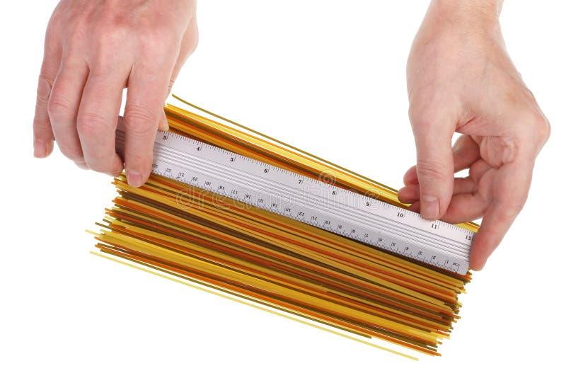 Rolnik sprawdza wielkość i jakość spaghetti warzywnych za pomocą wyizolowanego makra obrazy royalty free