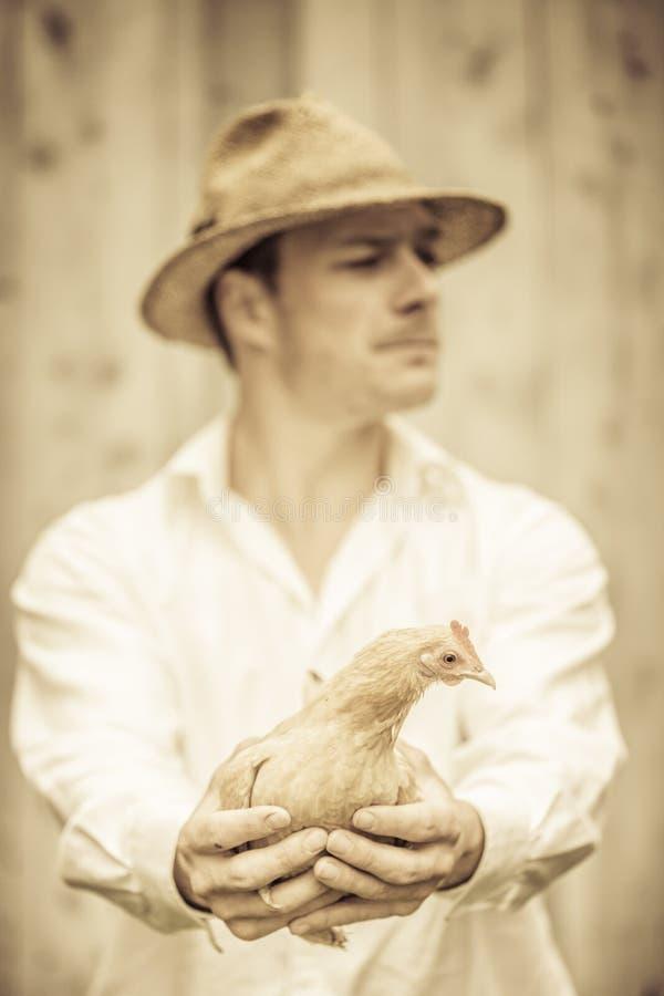 Rolnik Trzyma Beżowego kurczaka obraz royalty free