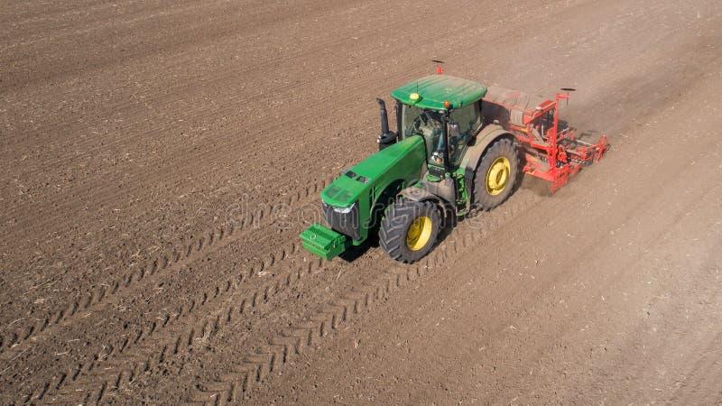 Rolnik z ciągnikiem z ikrzakiem, wysiewne obsiewanie uprawy przy rolniczym polem widok z lotu ptaka obraz royalty free