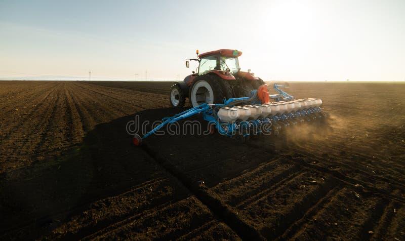 Rolnik z ci?gnikowymi obsiewanie soj uprawami przy rolniczym polem zdjęcie stock