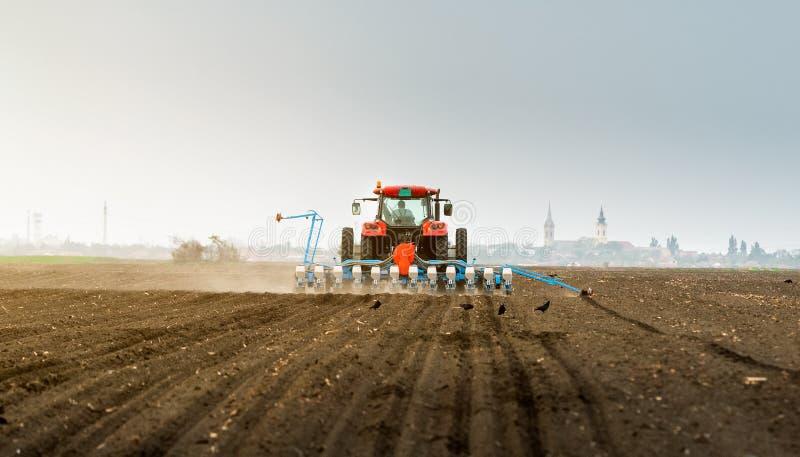 Rolnik z ci?gnikowymi obsiewanie soj uprawami przy rolniczym polem zdjęcia royalty free