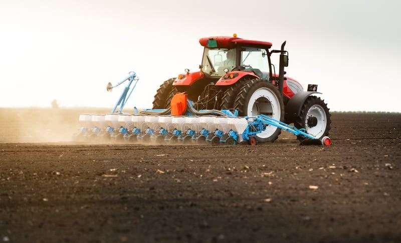 Rolnik z ci?gnikowymi obsiewanie soj uprawami przy rolniczym polem fotografia royalty free