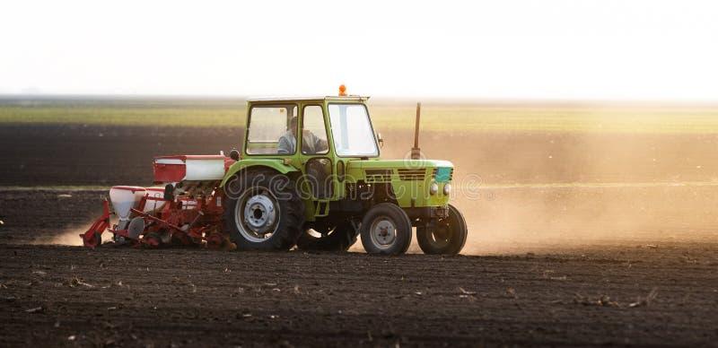 Rolnik z ci?gnikowymi obsiewanie soj uprawami przy rolniczym polem zdjęcia stock