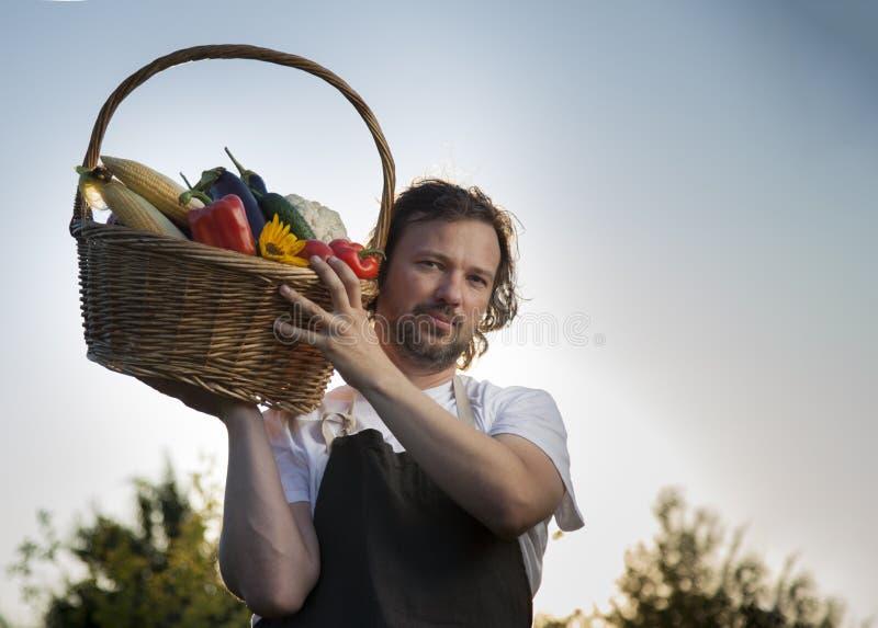 Rolnik z ekologicznym zbiorem warzyw w koszyku w pobliżu łóżek ogrodowych latem fotografia royalty free