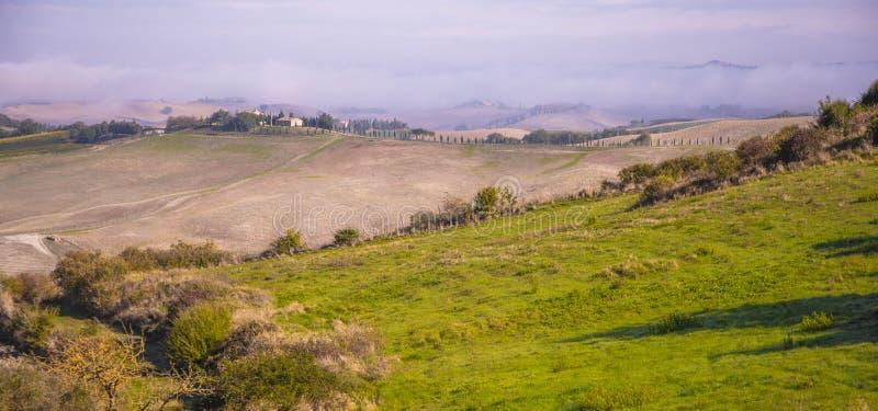 Rolny dom siedzi przy wierzchołkiem wzgórze pod mgłą w Tuscany zdjęcia royalty free
