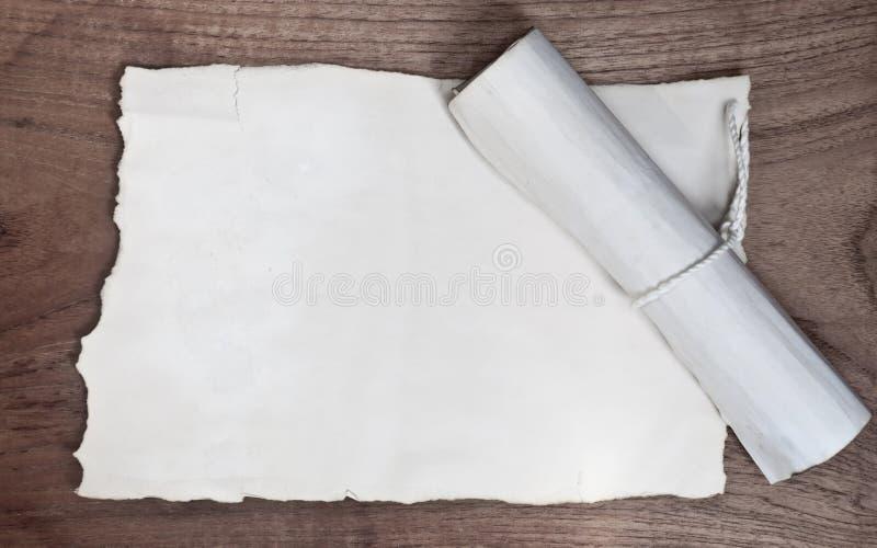 Rolo antigo com papel na tabela de madeira imagens de stock royalty free