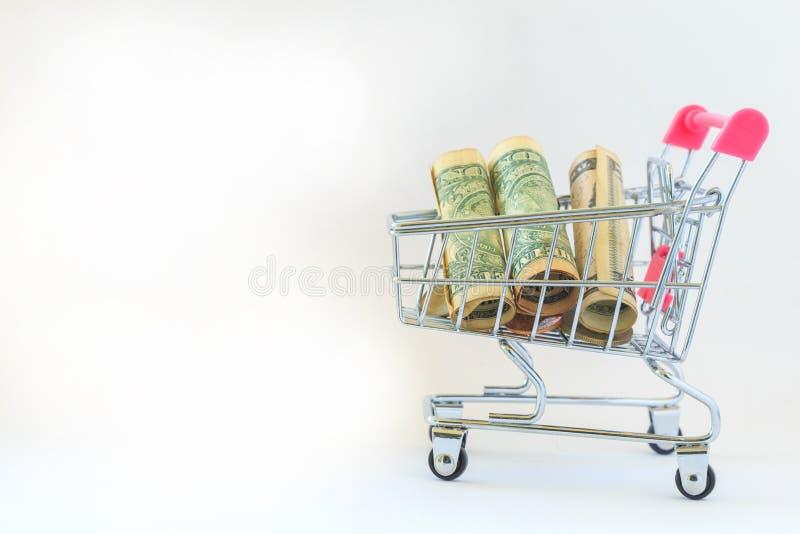 Rolo da cédula no mini carrinho de compras cor-de-rosa na tabela branca com whi fotos de stock