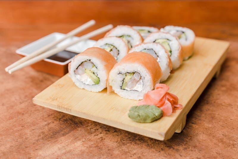 Rolo da causa com molho do gengibre, do wasabi e de soja em uma tabela de madeira foto de stock royalty free