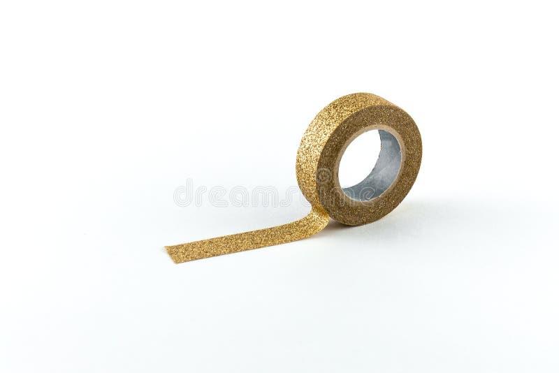 Rolo da fita de máscara dourada no fundo branco foto de stock royalty free