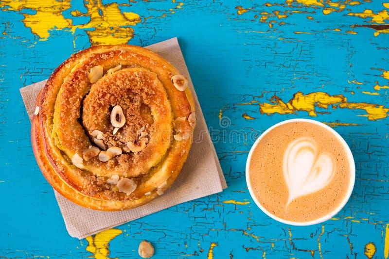 Rolo da pastelaria do cappuccino e da canela no descascamento e madeira pintada azul e amarela rachada de cima de Espa?o para o t fotos de stock royalty free