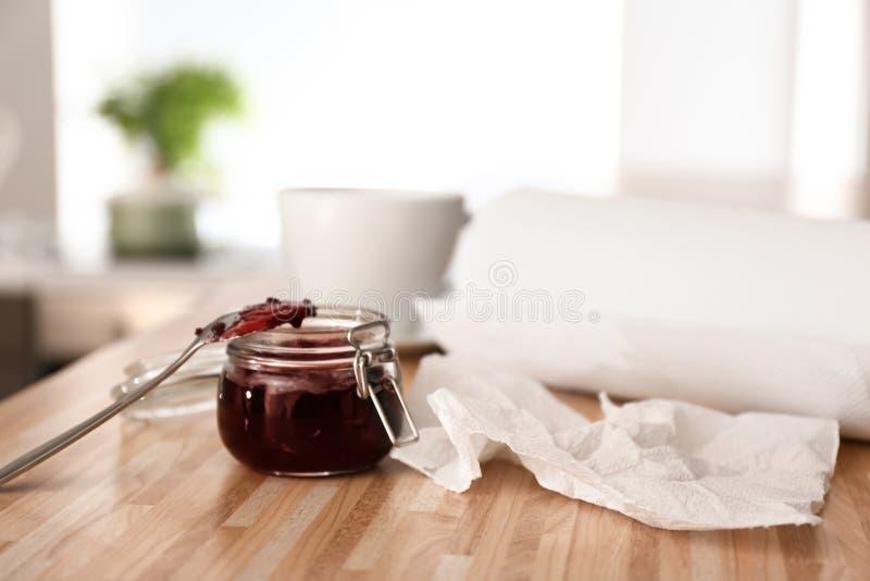 Rolo das toalhas de papel com o frasco do doce na mesa de cozinha foto de stock royalty free