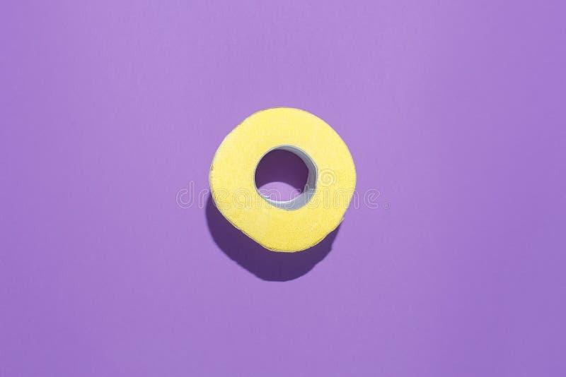 Rolo de papel higiênico amarelo em um fundo roxo Composição lisa fotografia de stock royalty free