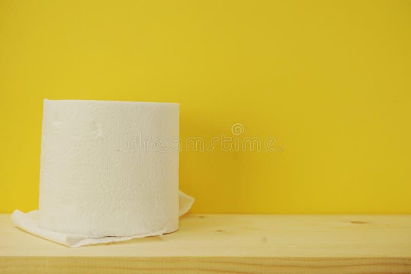 Rolo de papel higiênico no fundo amarelo imagem de stock royalty free