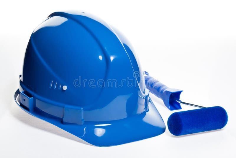 Rolo de pintura e capacete de segurança azul imagem de stock royalty free