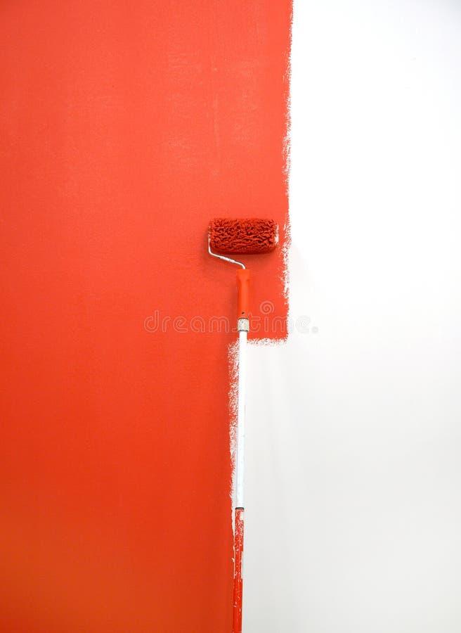 Rolo de pintura vermelho pela parede fotos de stock