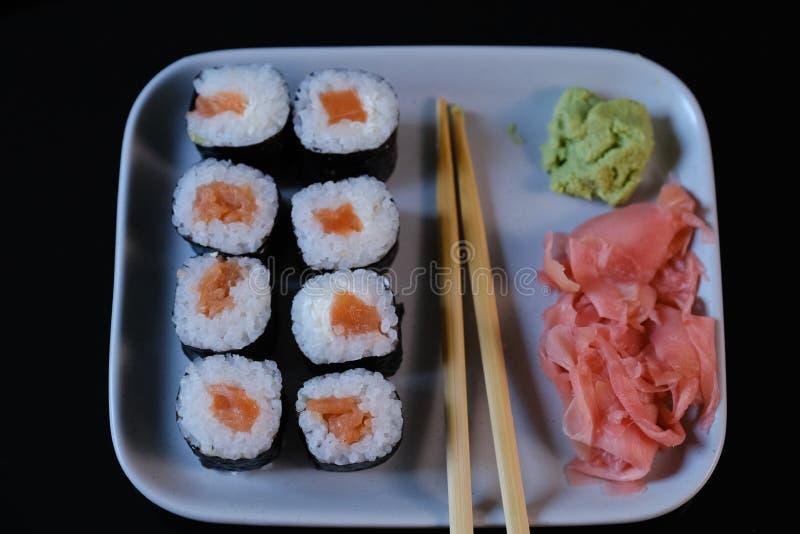 Rolo de sushi com molho do marisco e de soja, wasabi e gengibre Rolo de sushi em uma placa cinzenta fotografia de stock royalty free