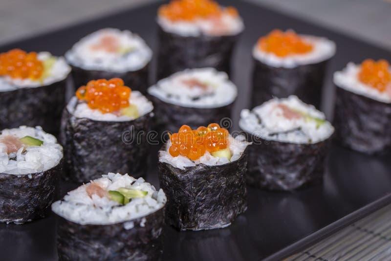 Rolo de sushi com salmões, pepino, abacate, caviar vermelho Menu do sushi Alimento japonês Fim acima imagem de stock