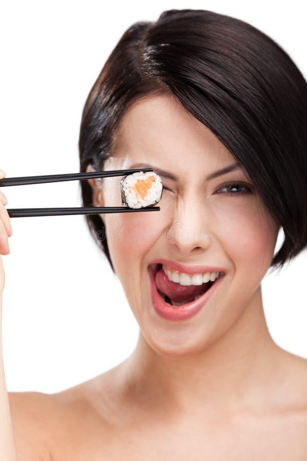 Rolo de sushi da terra arrendada da mulher nova com chopsticks imagens de stock royalty free