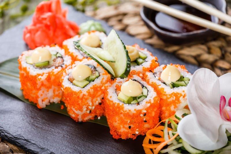 Rolo de sushi - Maki Sushi feita dos salmões, do caviar vermelho, do pepino, do abacate e do queijo creme na pedra preta na estei fotografia de stock