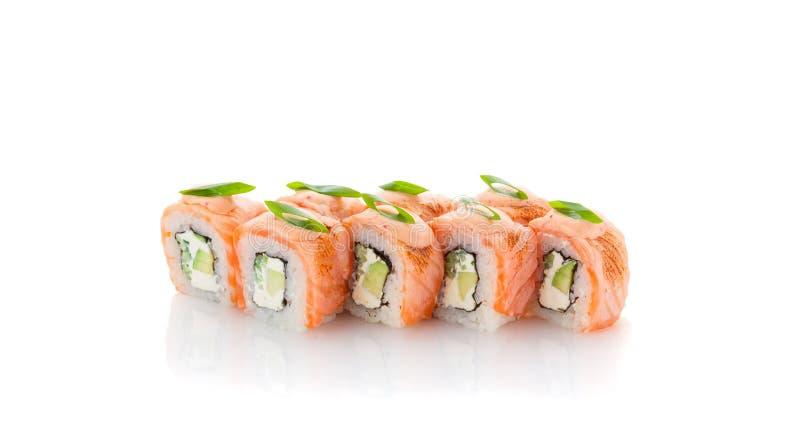 Rolo de sushi Salmon com o abacate, a cebola verde e o molho da especiaria isolados fotografia de stock