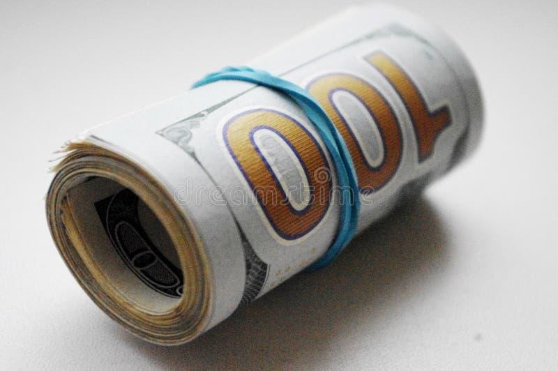 Rolo dos dólares amarrados com elástico no fundo branco imagem de stock royalty free