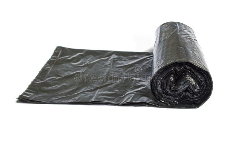 Rolo dos sacos de lixo descartáveis isolados sobre o branco fotografia de stock
