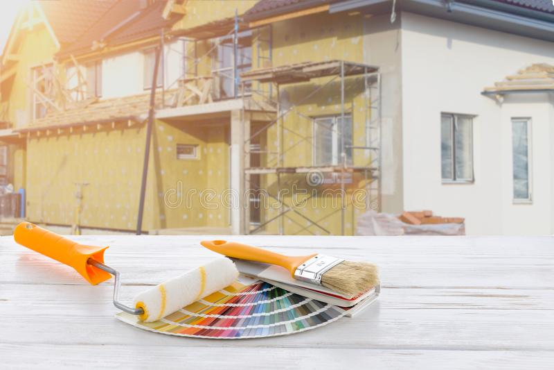 Rolo e escova de pintura na casa sob a construção fotos de stock