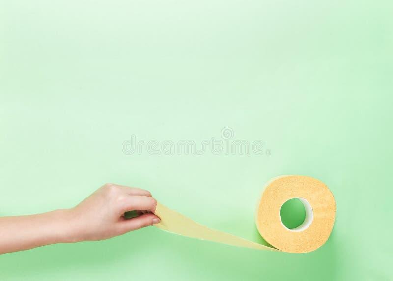 Rolo fêmea do papel higiênico do amarelo da posse da mão no fundo do verde-lima Vista superior Copie o espaço Na moda higiênico c foto de stock royalty free