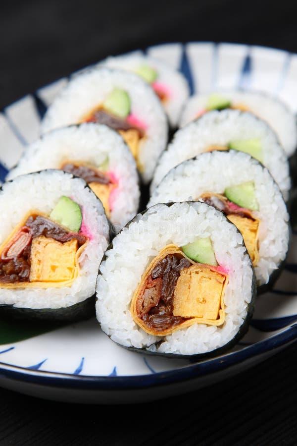 Rolo grosso do makizushi em uma mesa de jantar imagem de stock