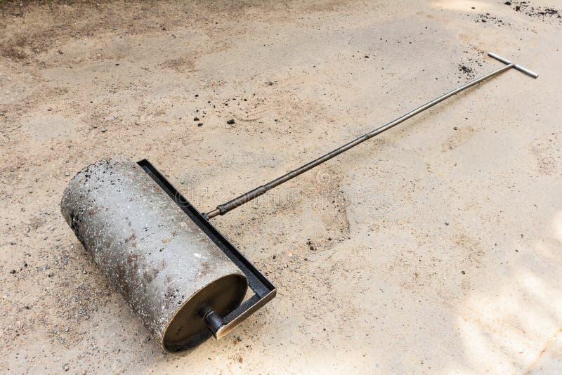 Rolo pesado da mão no fundo do asfalto fotografia de stock royalty free