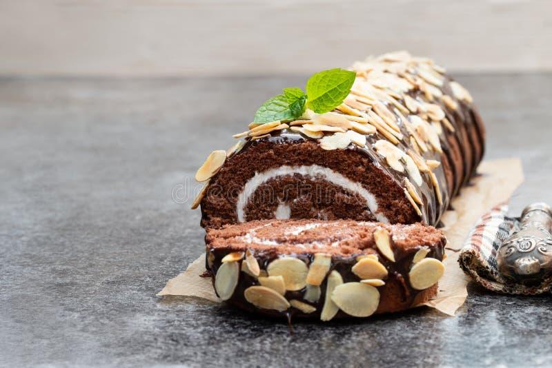 Rolo suíço do chocolate com os flocos da amêndoa na tabela cinzenta fotografia de stock royalty free
