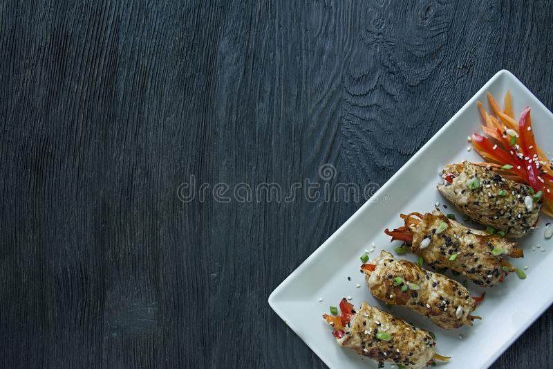 Rolos caseiros do peito de frango com verdes, fatias da cenoura, pimenta de sino em uma placa retangular leve O conceito da culin foto de stock
