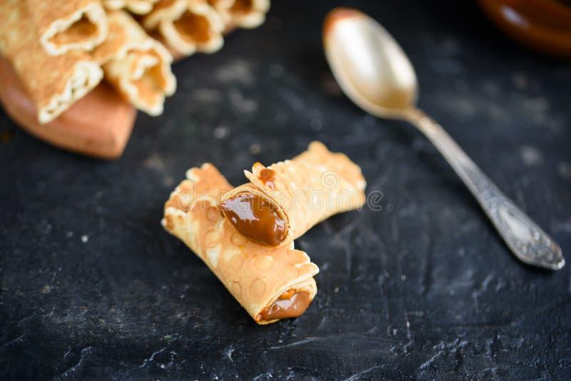 Rolos da bolacha, saboroso e perfumado, com leite condensado fervido em uma tabela preta fotografia de stock