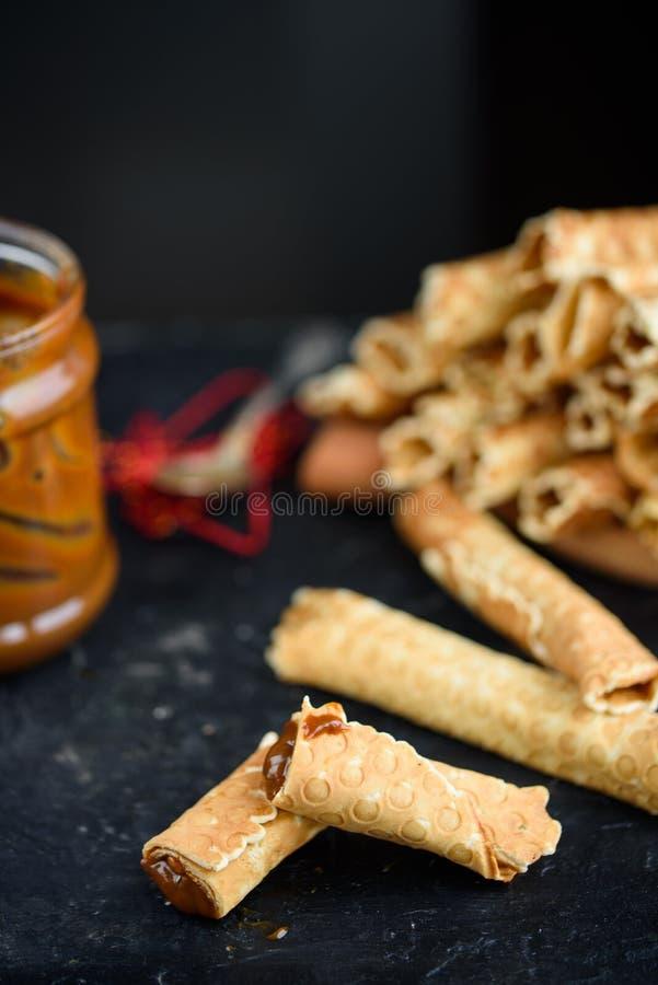 Rolos da bolacha, saboroso e perfumado, com leite condensado fervido em uma tabela preta foto de stock