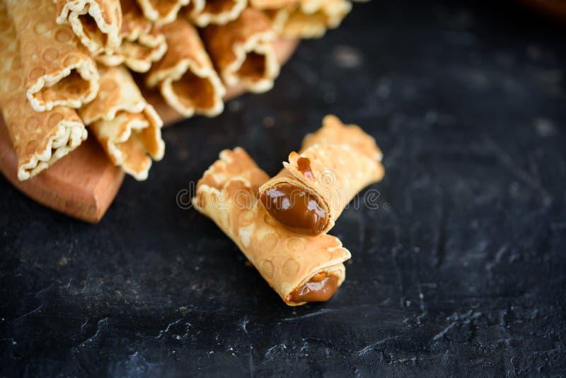 Rolos da bolacha, saboroso e perfumado, com leite condensado fervido em uma tabela preta imagem de stock