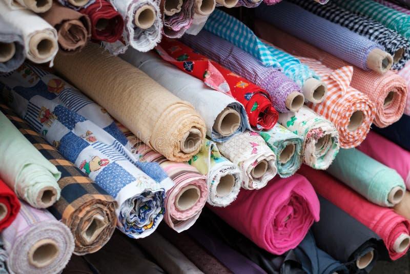 Rolos da tela e matérias têxteis coloridas no suporte do mercado imagem de stock royalty free