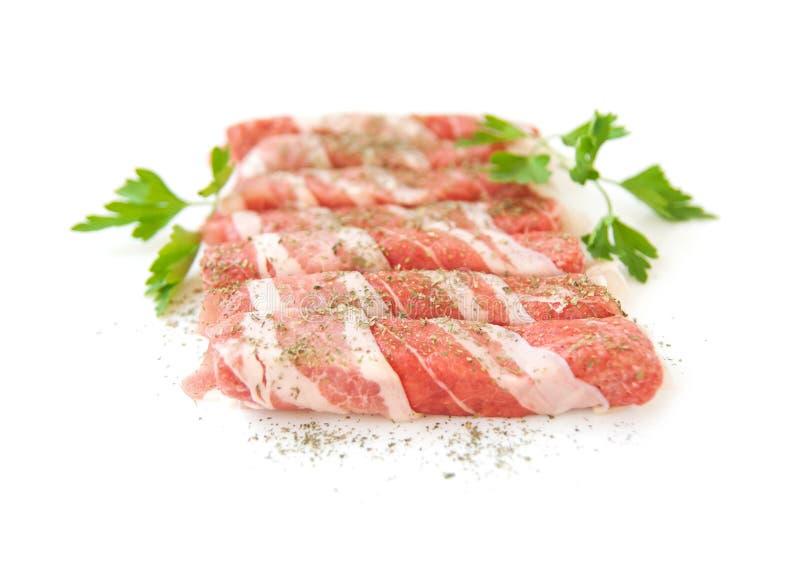 Rolos de carne fresca com as especiarias isoladas no fundo branco imagem de stock